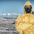 Stock Photo: Worker in protective chemical suit over mountains.