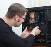 Male technician repairing computer at store — Stock Photo