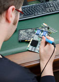 Worker repairing computer equipment with soldering iron — Stock Photo