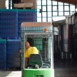 Stock Photo: Warehouse worker loading wine boxes by forklift