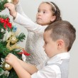 Stock Photo: Children decorating Christmas tree with balls.