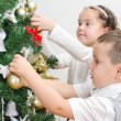 Children decorating Christmas tree with balls. — ストック写真