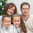 Happy family members sitting over christmas tree — Foto Stock