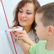 Little boy with teacher near whiteboard — Stock Photo #36290727
