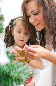 Woman and her daughter decorating the Christmas tree — Foto Stock