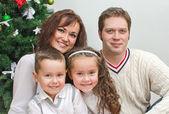 Happy family members sitting over christmas tree — Stock Photo