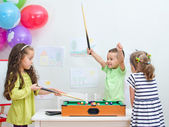 Children playing mini billiard at playroom — Stock Photo