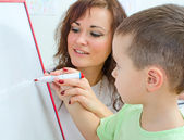 Little boy with teacher near whiteboard — Stock Photo