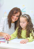 Teacher helps little girl to draw — Stockfoto