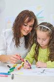 Teacher helps little girl to draw — Stock Photo