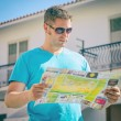 Young handsome man travel with a map in the town — Foto de Stock