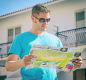 Young handsome man travel with a map in the town — Stock Photo