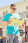 Young handsome man travel with a map in the town — Stok fotoğraf