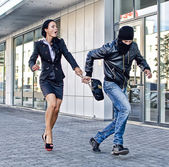 Bandit stealing businesswoman bag in the street — Stock Photo