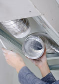 Male hands setting up ventilation system indoors — 图库照片