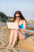 Woman with laptop working on the beach. — Stock Photo