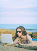 Woman with laptop working on the beach. Place for text. — Stock Photo
