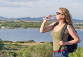 Female tourist tired. Drinking water. — Stock Photo