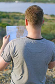 Male tourist with map on vacation. From the back. — Stock Photo