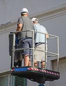 Elevador hidráulico com dois trabalhadores. — Fotografia Stock