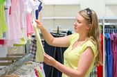 Woman shopping in children's clothing store. — Stock Photo