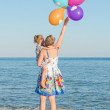 Little girl and her mother with balloons near the sea. — Stock Photo