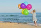 Little girl running with colorful balloons. — Stock Photo