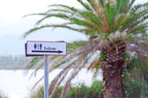Toilet sign with palm tree on backdrop. — Stock Photo