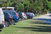 Cars parked in a parking lot on the grass. — Stock Photo