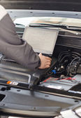 Mechanic with laptop diagnoses car in workshop. — Stock Photo