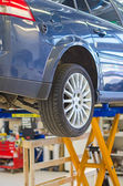 Car on lift in garage prepared for repair. — Stock Photo