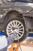 Mechanic changing car wheel at service. — Stock Photo
