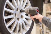Mechanic changing car wheel at service. — Stock Photo