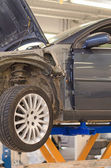 Car on lift in garage prepared for repair. — Foto Stock