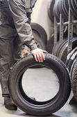 Mechanic holding car tire at warehouse. — Foto Stock