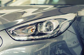 Car headlamp. Part of car at dealership salon. — Stock Photo