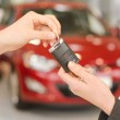 Female hand getting modern car key on a red car background — Stock Photo #45934973