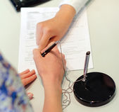 Female hands putting signature to agreement document in office — Stock Photo