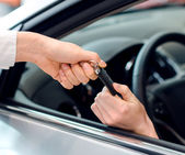 Closeup view of female hand inside the car getting keys — Stock Photo