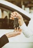 A chave do carro moderno sobre um fundo de carro de mão feminina — Fotografia Stock