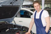 Young handsome mechanic standing near open car hood — ストック写真