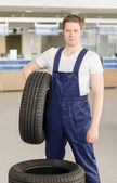 Young mechanic with tire in service center. — Stock Photo