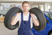 Young mechanic with tires in service center. — Stock Photo