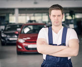 Young handsome mechanic in car dealership. Place for text. — Stock Photo