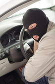 Thief in mask steals expensive new car. — Stock Photo