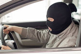 Thief in mask steals expensive new car. — ストック写真