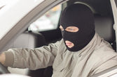 Thief in mask steals expensive new car. — Стоковое фото