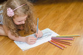 Little girl drawing car with colored pencils. — Stockfoto