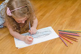 Little girl drawing car with colored pencils. — Foto de Stock