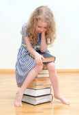Little girl with many books at home. — Stock Photo